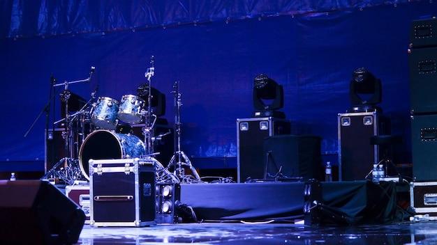 밴드가 공연을 할 준비가 된 푸른 빛의 무대에 설치된 드럼과 스피커 세트가있는 분위기있는 배경