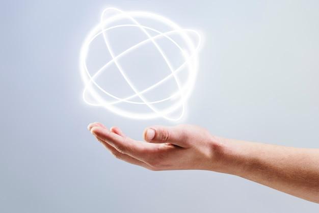 人間の手の科学技術のリミックスに表示される原子ホログラムの背景