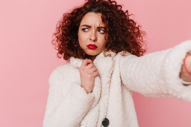 Atractive curly girl with red lips dressed in white wool coat makes selfie on pink isolated space.