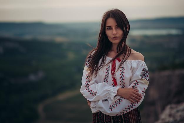 Привлекательная женщина в традиционном румынском костюме на горном зеленом фоне размытым