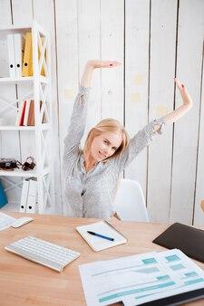 Привлекательная молодая деловая женщина, протягивая руки, сидя на своем рабочем месте