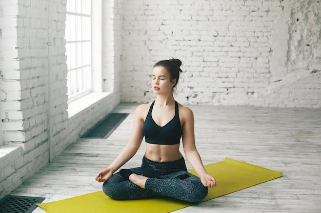 Attraente giovane donna caucasica che lavora a casa, facendo esercizi di yoga sul tappeto verde, seduto nella posa del loto con le gambe piegate e gli occhi chiusi, meditando, respirando profondamente, rilassando il corpo e la mente