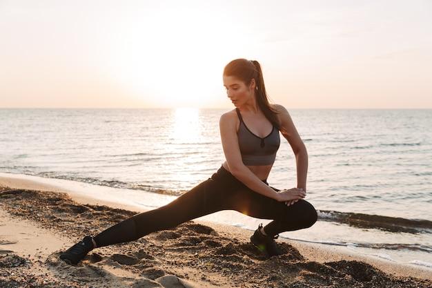 Привлекательная молодая спортсменка, тренирующаяся на пляже