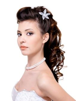 白で隔離される美しい結婚式のヘアスタイルを持つ魅力的な若い女性