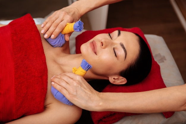 Attaching herbal bag. smiling woman with closed eyes being satisfied with unusual procedure in professional spa salon