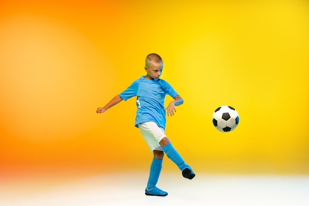 Attack. young boy as a soccer or football player in sportwear practicing on gradient yellow in neon light