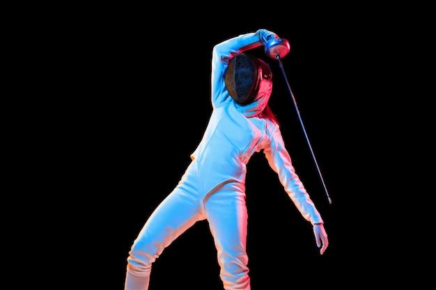 Attaccare. teen girl in costume da scherma con la spada in mano isolati su sfondo nero, luce al neon. modello giovane che pratica e si allena in movimento, azione. copyspace. sport, gioventù, stile di vita sano.