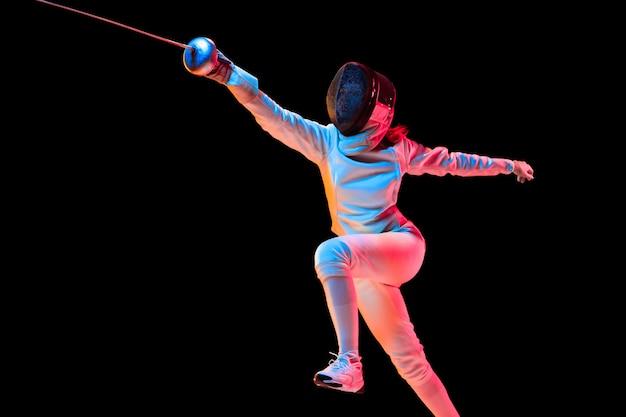 공격. 검은 배경, 네온 빛에 고립 된 손에 칼으로 펜싱 의상에서 십 대 소녀. 젊은 모델 연습과 운동, 행동 훈련. copyspace. 스포츠, 젊음, 건강한 라이프 스타일.