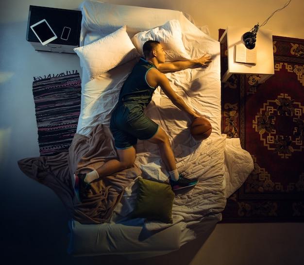 Атакующий вид сверху молодого профессионального боксера-бойца, спящего в своей спальне в спортивной одежде