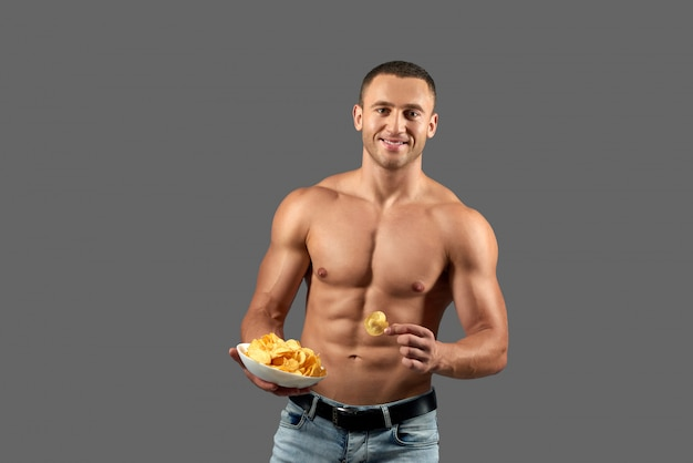 Attactive man smiling, holding bowl with chips.