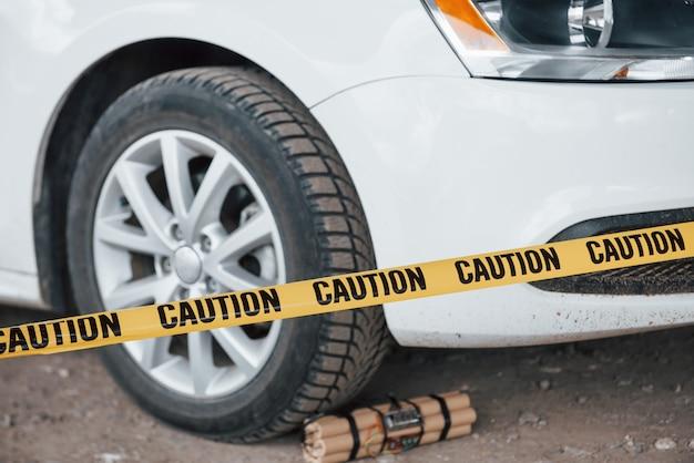 Попытка предотвращена. опасное взрывчатое вещество возле колеса современного белого автомобиля. желтая предупреждающая лента спереди