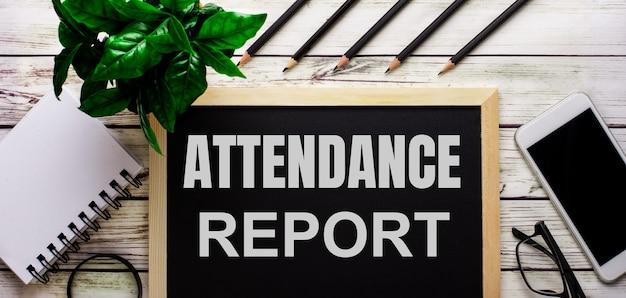 出席レポートは、電話、メモ帳、眼鏡、鉛筆、緑の植物の横にある黒い板に白で書かれています
