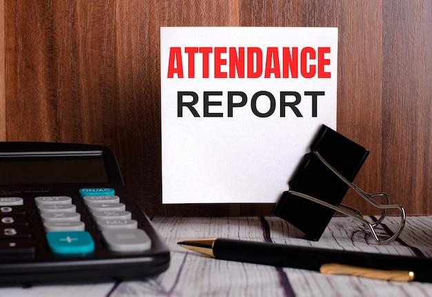 出席レポートは、電卓とペンの横にある木製の背景の白いカードに書かれています。