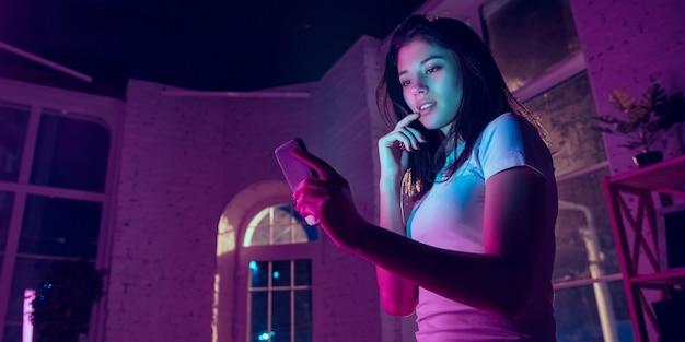주의를 기울였습니다. 네온 조명이 켜진 실내에서 잘생긴 세련된 여성의 영화적 초상화. 보라색 - 파란색의 영화 효과처럼 톤. 실내에서 화려한 조명으로 스마트폰을 사용하는 백인 여성 모델. 전단.