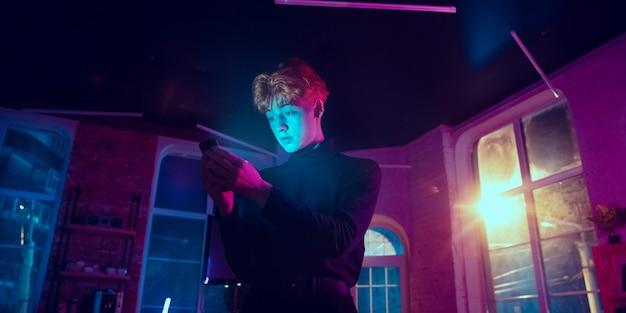 주의를 기울였습니다. 네온 조명 인테리어에 세련된 빨간 머리 남자의 영화 초상화. 보라색 - 파란색의 영화 효과처럼 톤. 실내에서 화려한 조명으로 스마트폰을 사용하는 백인 모델입니다. 전단.