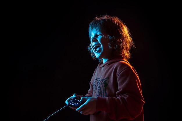 ビデオゲームのプレイに注意。ネオンの光の暗いスタジオの背景に白人の少年の肖像画。美しい巻き毛モデル。人間の感情、顔の表情、販売、広告、現代の技術、ガジェットの概念。