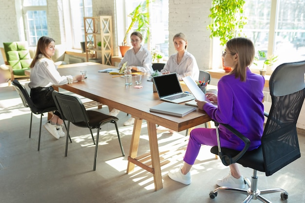 Attented. young caucasian business woman in modern office with team.