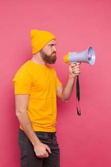 Attention! angry european man shouting in megaphone on pink background