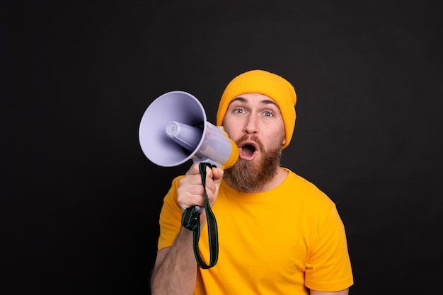Attention! european man shouting in megaphone on black background