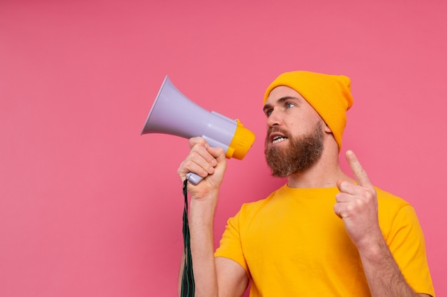 Attention! european man shouting in megaphone on pink background