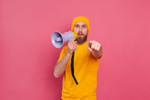 Attention! european man with megaphone pointing finger to camera on pink background