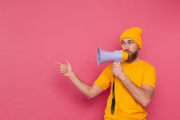 Attention! european man with megaphone pointing finger to the left on pink background