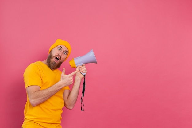 Attention! european man with megaphone pointing finger to the right on pink background