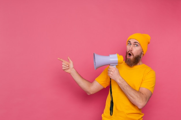 Внимание! европейский мужчина с мегафоном, указывая пальцем влево на розовом фоне