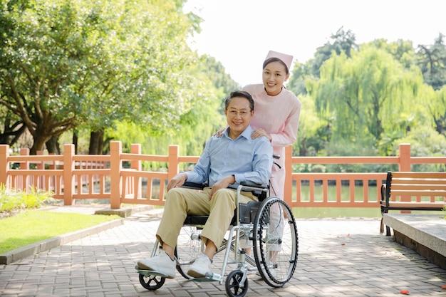 車椅子の老人と看護師の注意