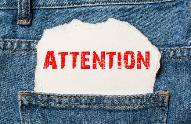 Внимание на белой бумаге в кармане джинсов синих джинсов
