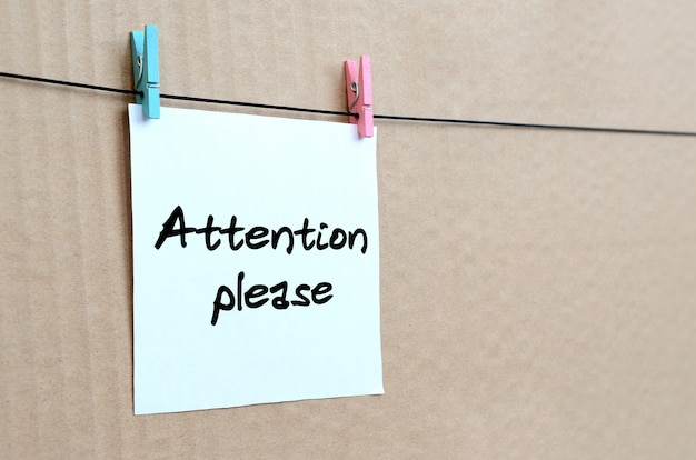 Attention please. note is written on a white sticker that hangs with a clothespin on a rope on a background of brown cardboard