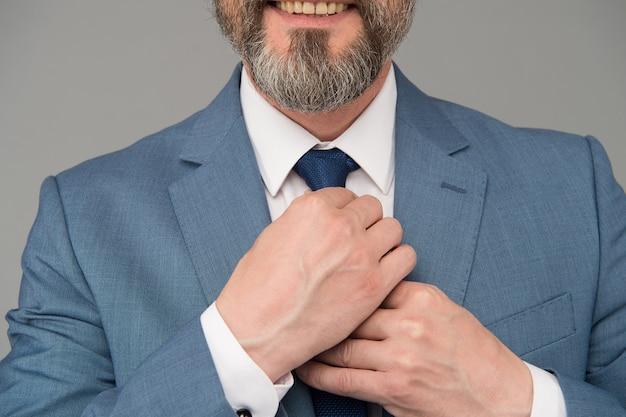 細部へのこだわり。男性の手はネクタイ灰色の背景を結びます。正式なネクタイコレクション。ネクタイを結ぶ。メンズアクセサリー。ファッションとスタイル。ドレスコード。スーツとネクタイ。