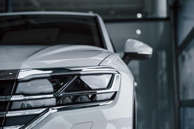 詳細への注意。昼間に屋内に駐車したモダンで豪華な白い車のパーティクルビュー