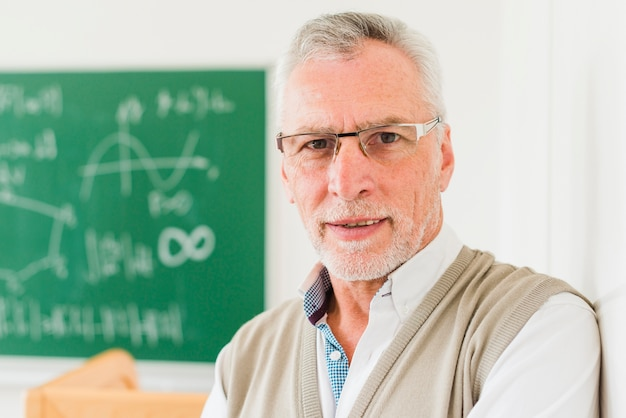 Attentive aged math teacher in glasses