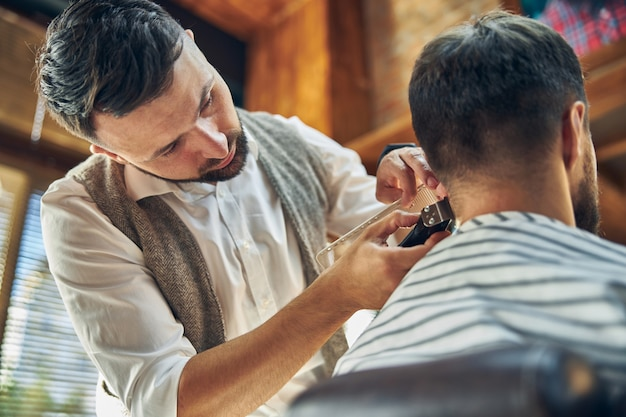 Attentive barber tilting his head while looking at his client and trimming his hair with electric clipper