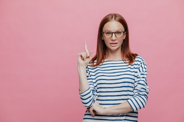 Attentive beautiful woman wears spectacles and striped sweater, points with fore finger upwards