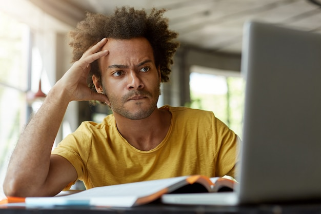 Attentive black young male sitting indoors in front of opened laptop being very serious while reading scientific article online trying to find main point of it and to write review on this topic