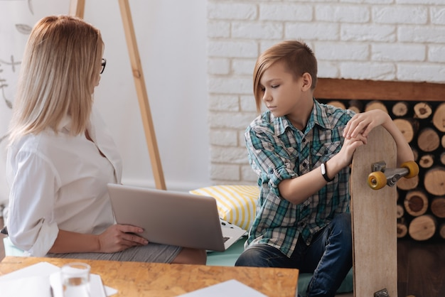 Attentive boy wearing casual clothes sitting near female looking on laptop