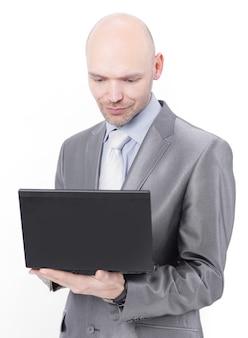 ノートパソコンを持って立っている気配りのある実業家。白い背景に分離