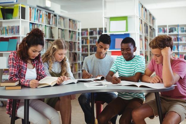 図書館で勉強している注意深い同級生