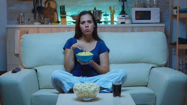 おやつを食べる映画を見ている注意深い集中若い女性。快適なソファに座ってサスペンス映画を見て驚いた顔をした夜の女性に一人でショックを受けた驚愕の家。