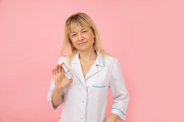 흰색 의료복을 입은 세심한 미용사 의사는 그녀의 손에 얼굴 관리 제품을 들고 있습니다. 과일산. 미용실.현대 화장품. 생활 양식. 휴식과 휴식. 중소기업.