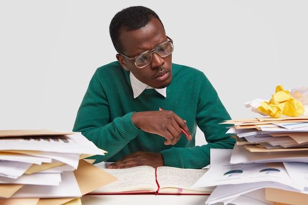 大きな眼鏡をかけた気配りのある暗い肌の男は、円グラフを真剣に見て、白い背景の上に隔離された緑のジャンパーを着て、ドキュメントを勉強した後にレポートを書きます。人