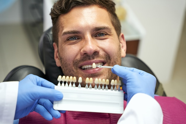Attentive dentist picking a right dental enamel colour