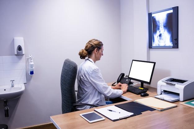 クリニックでコンピューターに取り組んでいる丁寧な医師