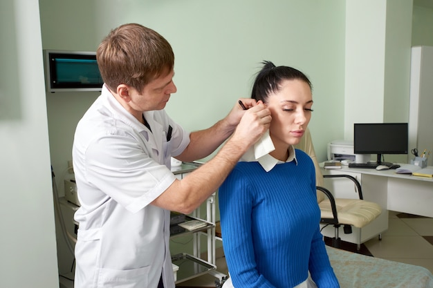 Attentive ent doctor doing ear exam of pretty woman