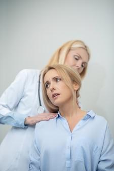 Внимательный опытный врач, ищущий причину боли при движении у пациента, исследующий шейный отдел позвоночника