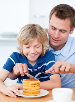 丁寧な父と彼の息子がワッフルを食べる