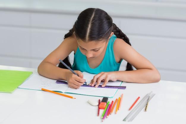 Attentive girl doing her homework in living room