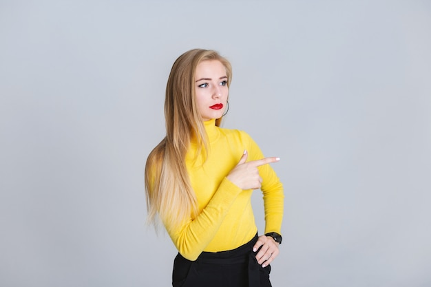 Attentive girl stands on a gray background and point aside with  her finger